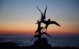 Sculptures en oiseau de sternes chez Skerrie sur un beau coucher du soleil Image libre de droits