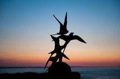Sculptures en oiseau de sternes chez Skerrie sur un beau coucher du soleil Image stock