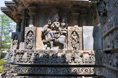 Sculptures on the fa ade, west side walls. Shiva-Parvati on sitting Nandi. Hoysaleshwara temple, Halebidu, Karnataka. India royalty free stock photography