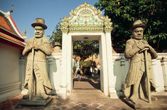 Sculptures of Farang guards at entrance of historical monastery Stock Image