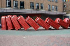 Sculpture `Out of Order` by David Mach, Kingston Upon Thames, England, United Kingdom. The sculptures features 12 old fashioned red English telephone booths stock photography