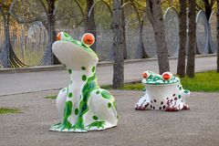 Sculptures of funny frogs in the shade of trees royalty free stock images