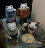 Sculptures heureuses en chat dans la robe traditionnelle et les activités Photos stock