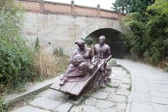 The sculptures of the husband and wife moving in the Jinniu ancient road in Deyang, Sichuan, China. The sculptures of the husband and wife moving Stock Photography