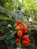 Sculptures in a japanese garden. Sculpture in a japanese garden with distinctive flowers in the foreground Royalty Free Stock Photos
