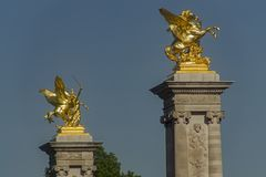 Sculptures on pedestals. Gold-plated sculptures on the pedestals of the Alexander Bridge in Paris Stock Photography