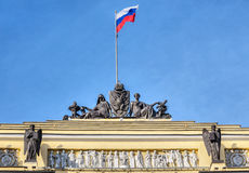 Sculptures and the Russian flag on building of the Synod and the Senate, St.-Petersburg. Sculptures and the Russian flag on an arch of a building of the Synod royalty free stock photos
