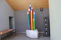 Sculpure av färgade blyertspennor för hand ett innehav Arkivbild