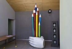 Sculpure av färgade blyertspennor för hand ett innehav Royaltyfri Foto