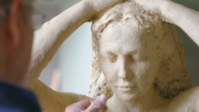 Scultor modeling woman sculpture in modeling clay stock footage