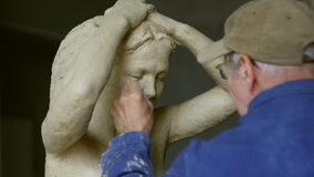 Scultor modeling woman sculpture in modeling clay stock video footage