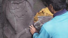 Scultore asiatico scrupoloso scheggiando via all'indennità dettagli complessi di un'opera d'arte di pietra facendo uso di un trad video d archivio