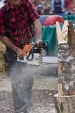 Scultore della motosega che scolpisce la scultura del ceppo