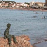 Scultura bronzea del bambino con protagonista alla spiaggia Immagine Stock