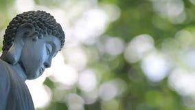 Scultura bronzea di Buddha nella posa di seduta tradizionale di meditazione sul fondo di Bokeh video d archivio