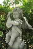 Scultura dell'angelo del bambino decorata in giardino Fotografie Stock