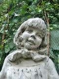Scultura della bambina e vite verde in giardino inglese Immagine Stock