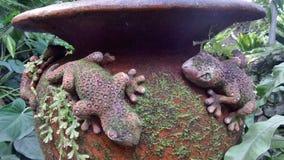 Scultura di Clay Gecko con muschio verde sul barattolo dell'acqua in giardino Immagine Stock