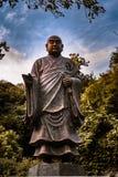 Scultura di Kamakura Buddah che esamina il cimitero ed il tempio fotografie stock