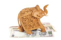 Scultura di legno dell'elefante sulle banconote della rupia indiana fotografia stock