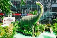Scultura di un modello della valle del dinosauro in un parco tropicale del giardino del grande magazzino fotografia stock libera da diritti