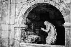 Scultura di un pregare dell'uomo anziano Fotografia Stock