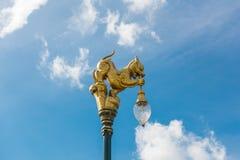 Scultura dorata del leone con il fondo del cielo blu, Tailandia fotografia stock