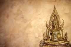 Scultura dorata di Buddha sul fondo goldish della parete Immagini Stock Libere da Diritti