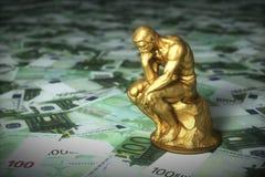 Scultura dorata di un pensatore che pensa sopra le euro banconote fotografie stock