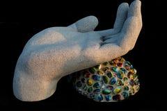 Sculture向手色的珠宝扔石头有黑背景 免版税库存照片