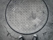 Road drain cover and sneakers. On the street Stock Photos