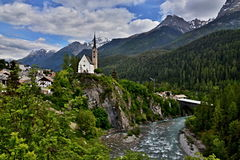 Scuol-view of the bridge and the church. Swiss Alps,Engadin-view of the bridge over the river Inn and the church in Scuol, in the background of snow-capped Alps Royalty Free Stock Images
