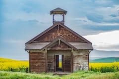 Scuola abbandonata che si siede nei campi di Canola nell'Oregon centrale Immagini Stock