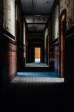 Scuola abbandonata per i ragazzi - corridoio con le pareti della pittura della sbucciatura e delle mattonelle - New York fotografia stock libera da diritti