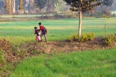 Scuola andante di Childern attraverso terreno coltivabile nella mattina fotografia stock libera da diritti