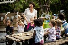 Scuola dei bambini e dell'insegnante che impara giardinaggio di ecologia fotografia stock