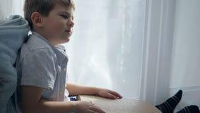 Scuola del bambino cieco e sveglio che legge la fonte di Braille che si siede sul davanzale nella sala stock footage