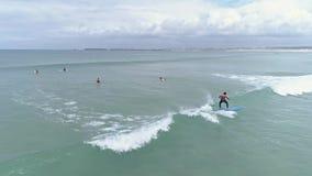 Scuola della spuma che impara antenna lenta praticante il surfing 4k video d archivio