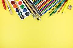 Scuola e articoli per ufficio pronti per gli allievi su fondo giallo Immagine Stock