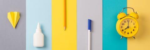 Scuola e articoli per ufficio su fondo a strisce luminoso concetto: di nuovo alla scuola, minimalismo Bandiera lunga fotografia stock
