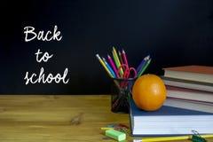 Scuola e articoli per ufficio sulla tavola dell'aula davanti a blackb Fotografie Stock