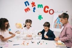 Scuola elementare che lavora con i modelli molecolari alla classe di chimica Immagini Stock