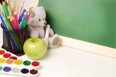 Scuola o articoli per ufficio con le pitture dell'acquerello della lavagna, le matite colorate e gli indicatori, primo piano Immagini Stock