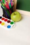 Scuola o articoli per ufficio con le pitture dell'acquerello della lavagna, matite colorate ed indicatori, isolati su fondo bianc Fotografie Stock
