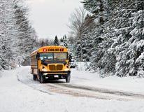 Scuolabus che guida giù una strada rurale innevata - 2 Fotografia Stock
