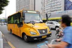 Scuolabus giallo che guida sulla strada ammucchiata Fotografia Stock
