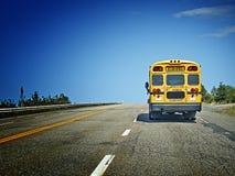 Scuolabus sulla strada da dietro Immagini Stock Libere da Diritti