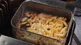 Scuotendo le patate fritte in un cesto metallico poi per immergerle ancora in olio bollente archivi video