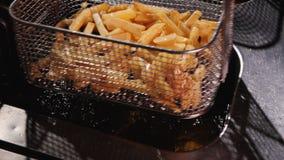 Scuotendo olio dalle patate fritte che preparano essere servito - movimento lento archivi video