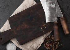 Scure d'annata del coltello della carne sul tagliere d'annata e sul fondo di pietra nero della tavola Utensili del macellaio Sale immagine stock